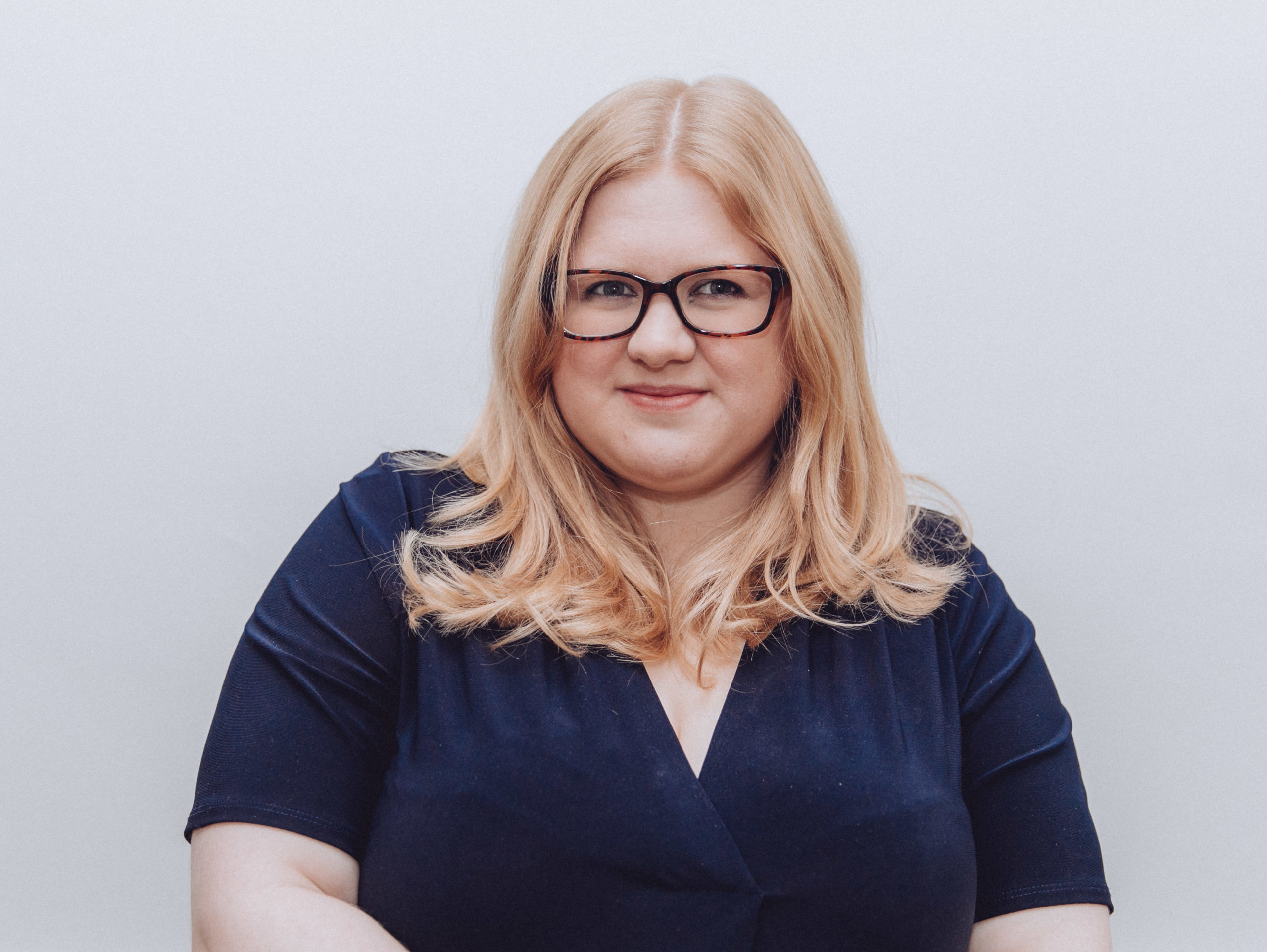 A headshot. Amy is a blonde white plus size woman wearing glasses. She is half smiling at the camera and wears a navy dress