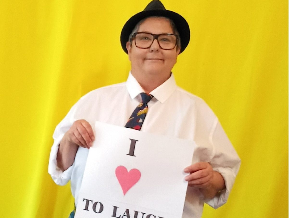 Image is a photo of Angela de Castro smiling at the camera holding a sign which says I love to laugh