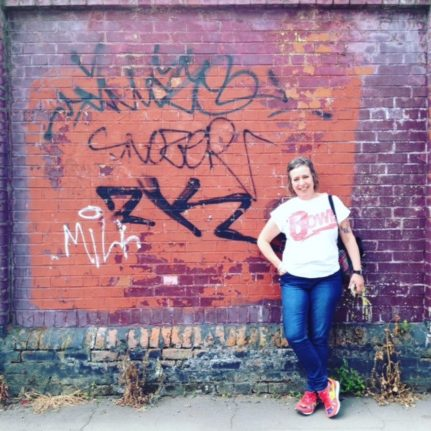 Image is a photos of Mairi standing next to a graffiti wall