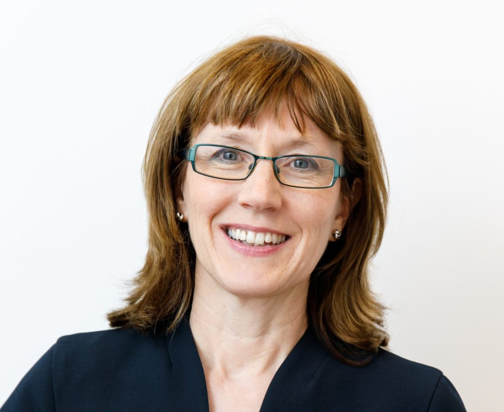 Image is a head and shoulders image of Philippa smiling at the camera. Philippa is wearing a black top and glasses.